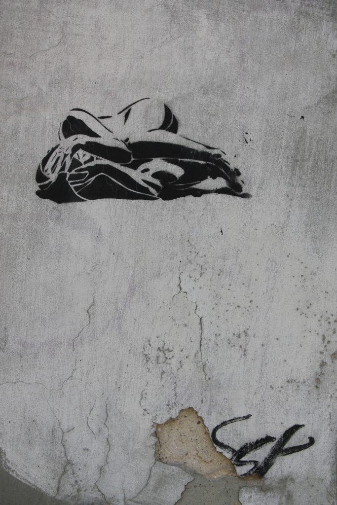 Zdjęcie przedstawia wykonaną szablonem isprejem postać kobiety, którależy itrzyma się rękami zagłowę. Głowa okryta jest szalem lub całunem