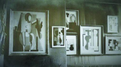 Zdjęcie przedstawia obrazy pokazane nawystawie wGalerie Aubier wParyżu w1928 roku, naobrazach widać geometryczne formy, wktórychujęte są przedmioty ipostaci ludzkie