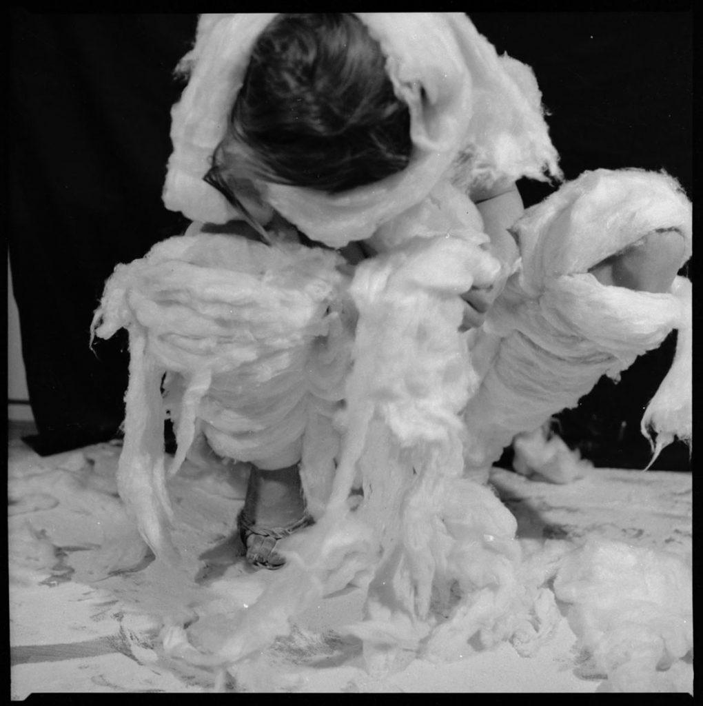 Na czarno-białej fotografii kobieta kuca zrozchylonymi nogami, schyla głową nisko, jest obleczona wduże kawałki białej waty.