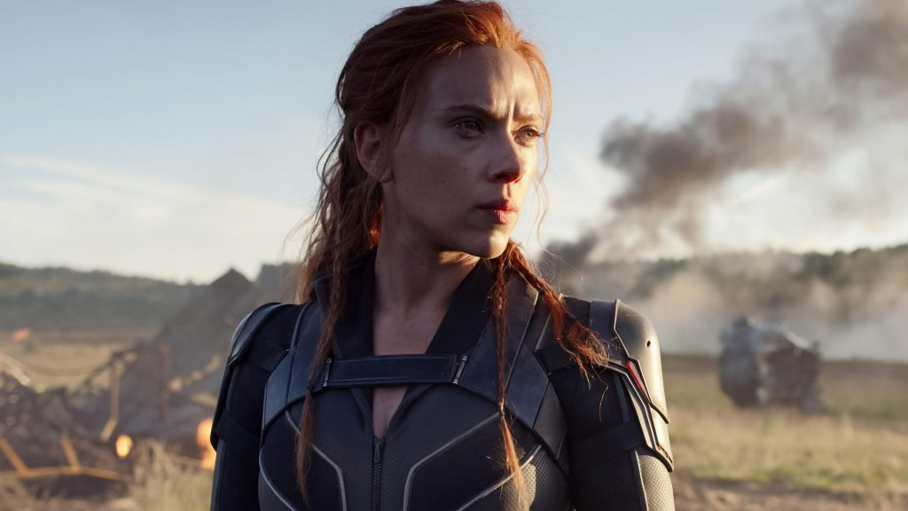 Kobieta orudych włosach, wskórzanej zbroi lub kostiumie bohaterki, stoi natrawiastym polu, wtle wraki bliżej nieokreślonych pojazdów lub przedmiotów, kilka smug dymu
