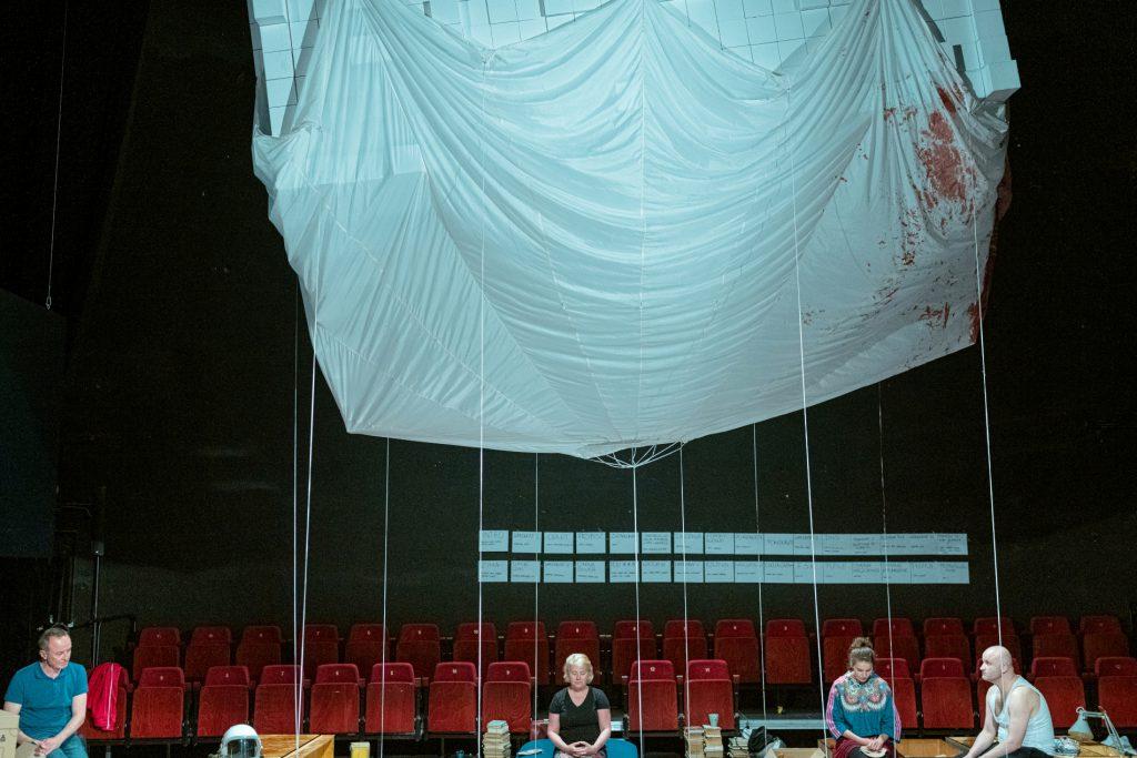 W kadrze dominuje zwisający spod sufitu lekki materiał zdoczepionymi taśmami, któraopadają prosto wdół nascenę. Oddołu widać dwa rzędy czerwonych krzeseł orazcztery zrezygnowane osoby siedzące wróżnych miejscach sceny