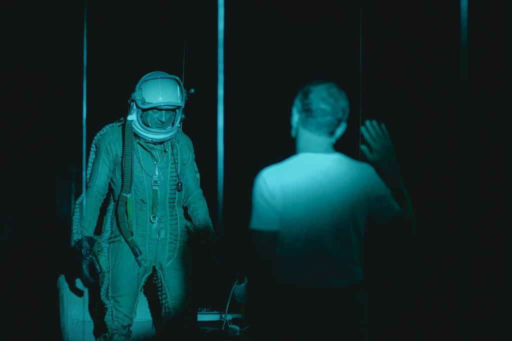 Po lewej stronie stoi mężczyzna wkompletnym stroju jakby astronauty, zotwartym hełmem. Przednim, plecami dopatrzącego, stoi drugi mężczyzna wbiałej koszulce, podnosi prawą rękę jakby wpowitaniu. Nascenie panuje mrok, światło pada naplecy drugiego zmężczyzn.