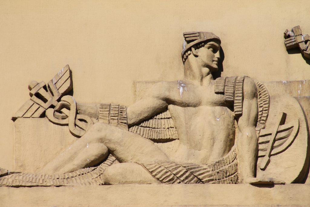 Wizerunek półleżacego boga Merkurego zkaduceusz, obiera się owizerunek łodzi, herb miasta.