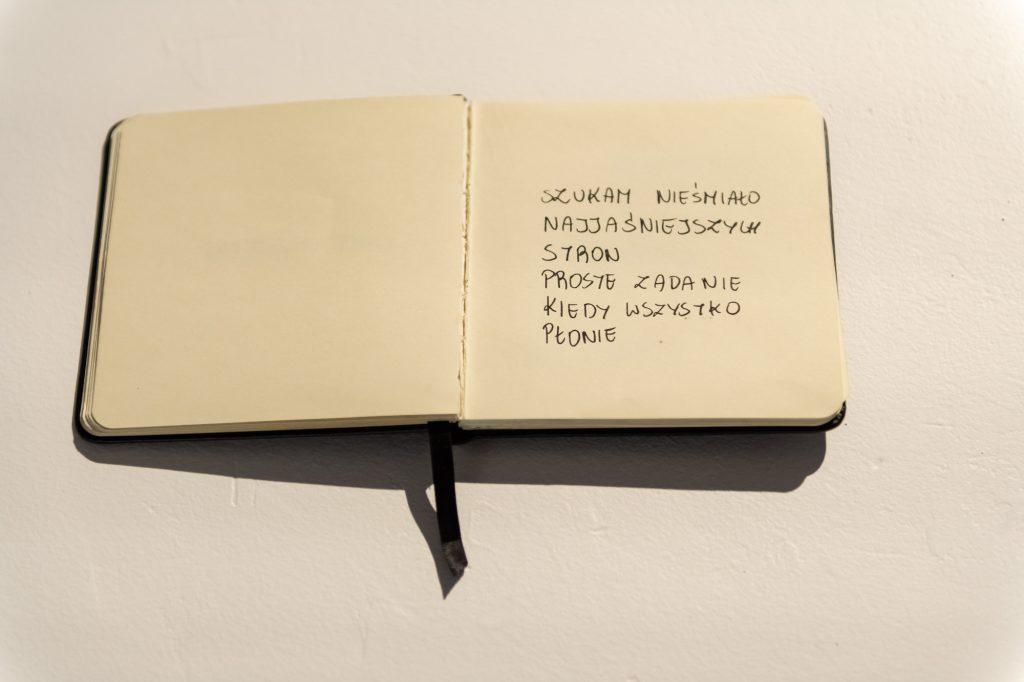 Jedna zprac pokazywanych nawystawie Kwadratowy notatnik otwarty nastronie gdzie dużymi literami napisano szukam nieśmiało najjaśniejszych stron proste zadanie kiedy wszystko płonie
