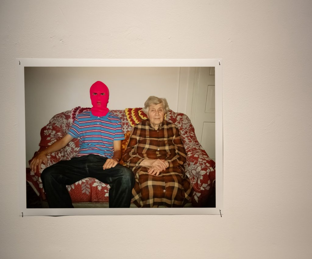 Fotografia, naktórejsiedzą poobok siebie stara kobieta, najpewniej babcia, zezłożonymi naudach dłońmi, obok młody szczupły chłopak wpolówce iróżowej wełnianej kominiarce nagłowie