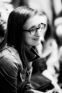 Zdjęcie młodej kobiety, widoczna jest ona zprawego półprofilu, lekko uśmiecha się, ma okulary wgrubych oprawkach