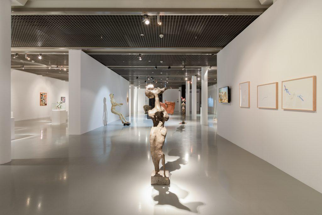 W centrum kadru rzeźba przypominająca pokawałkowanego człowieka. Naprawo doniej biała ściana zpowieszonymi niedużymi obrazami. Wdalszym planie między innymi rzeźba przypominająca opierającą się ościanę postać ludzką, ścianki działowe wystawy, postumenty zmniejszymi rzeźbami.