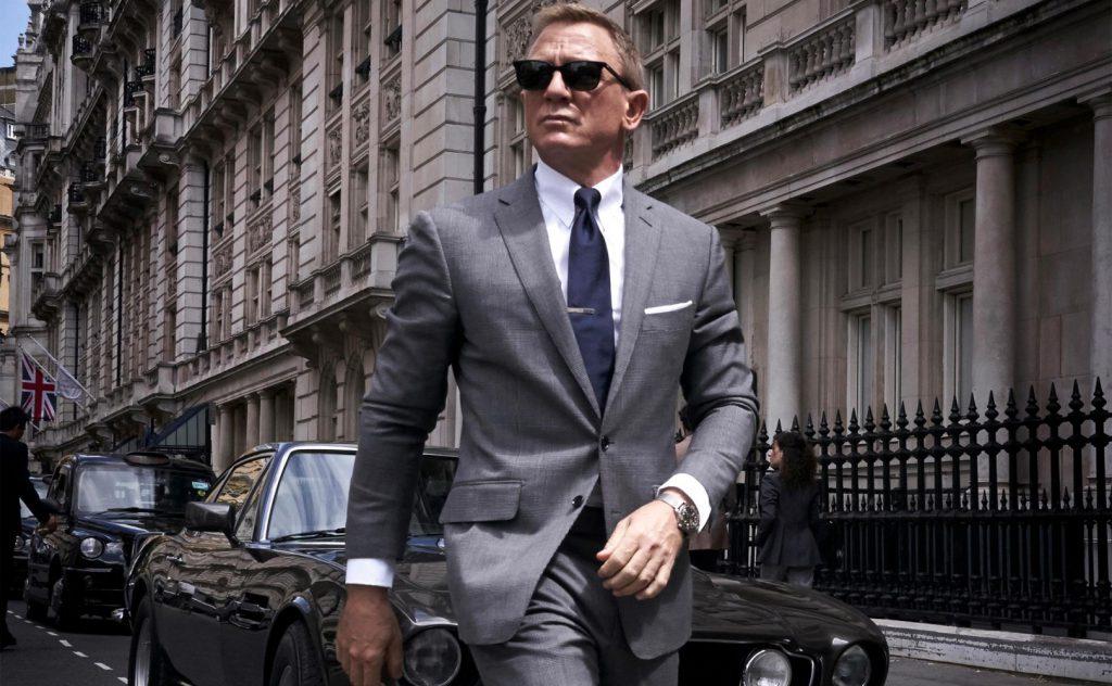 Daniel Craig jako James Bond weleganckim garniturze idzie ulicą miasta, wtle ma drogie samochody, natwarzy okulary