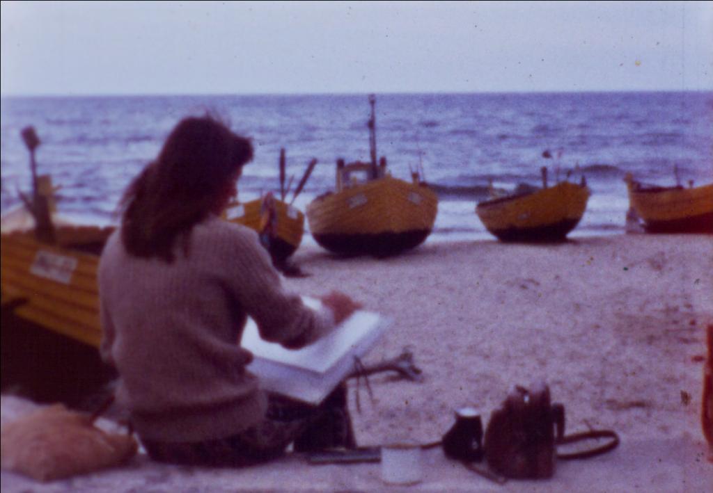 Kobieta siedząca zeszkicownikiem naplaży, wtle kilka rybackich żółtych kutrów. Obok niej leży torba itermos. Obraz jest niewyraźny, akolory przebarwione wkierunku niebieskiego iczerwonego.
