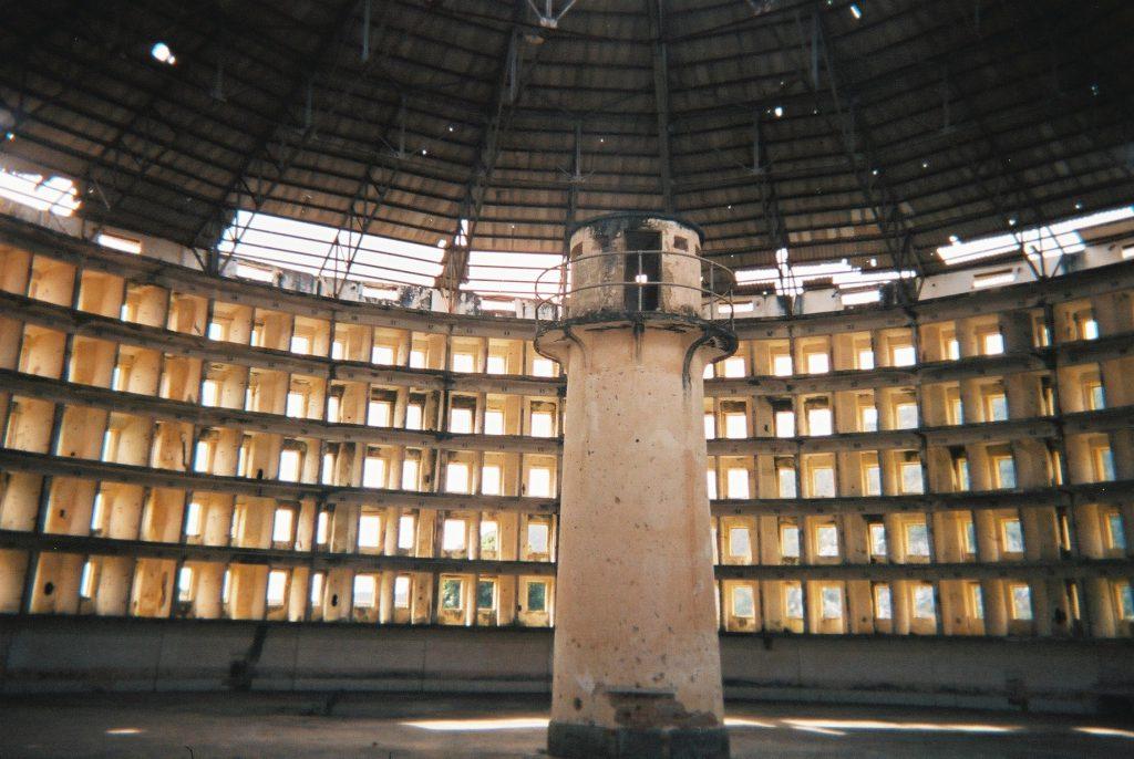 Widok kubańskiego więzienia, gdzie pośrodku postawiono strażnicę którawygląd jak latarnia, otoczona jest owalną ścianą więzienia, wktórejzaprojektowano małe dobrze widoczne zestrażnicy cele