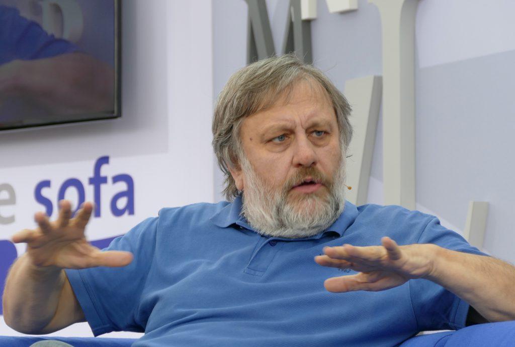 Filozof Slavoj Žižek rozparty nakanapie, gestykuluje