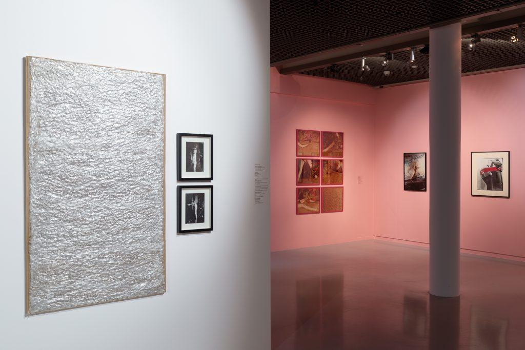 Na pierwszym planie najasnej ścianie srebrna prostokątna praca idwa mniejsze ciemne zdjęcia wramkach obok. Wtle różowe ściany iszereg mniejszych iwiększych prac