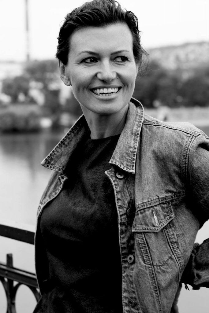 Pisarka Bianka Bellova stoi oparta oporęcz mostu, uśmiecha się szeroko, patrzy przezswoje lewe ramię