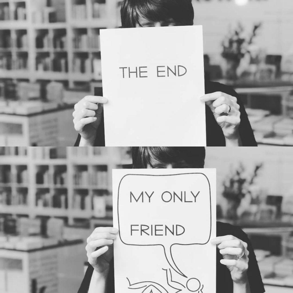 """dwa podobne zdjęcia, napierwszym dziewczyna zakrywa twarz kartką zanapisem koniec, nadrugim odwraca kartkę ijest napis mójjedyny przyjacielu. Jest tocytat zpiosenki The Doors """"The End"""""""