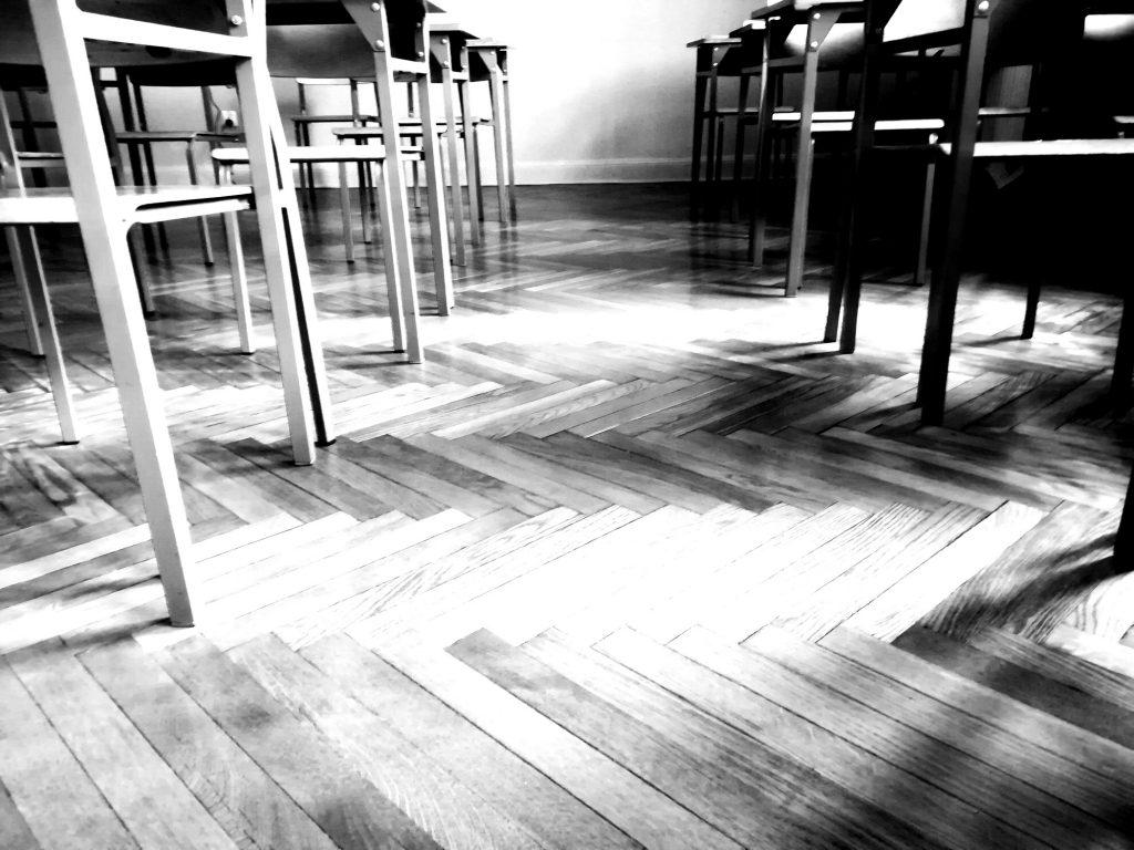 widok drewnianej podłogi wklasie szkolnej, rządy nóg ławek ikrzeseł, bezuczniów