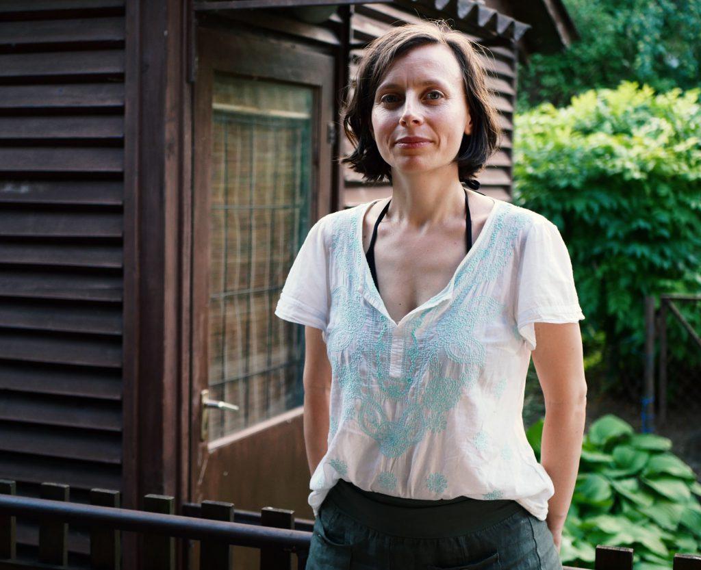 Pisarka Réka Mán-Várhegyi wbiałej cienkiej koszuli, stoi natle drzwi dobrązowego domku lub altany.